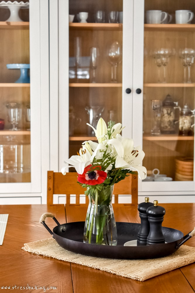 Spring flowers in a carafe on a dining room table
