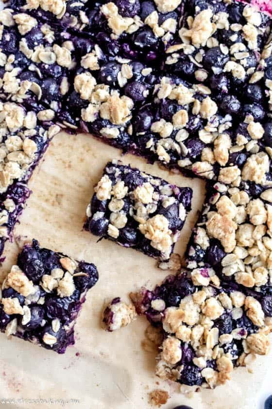 Overhead shot of sliced blueberry oatmeal bars on parchment paper
