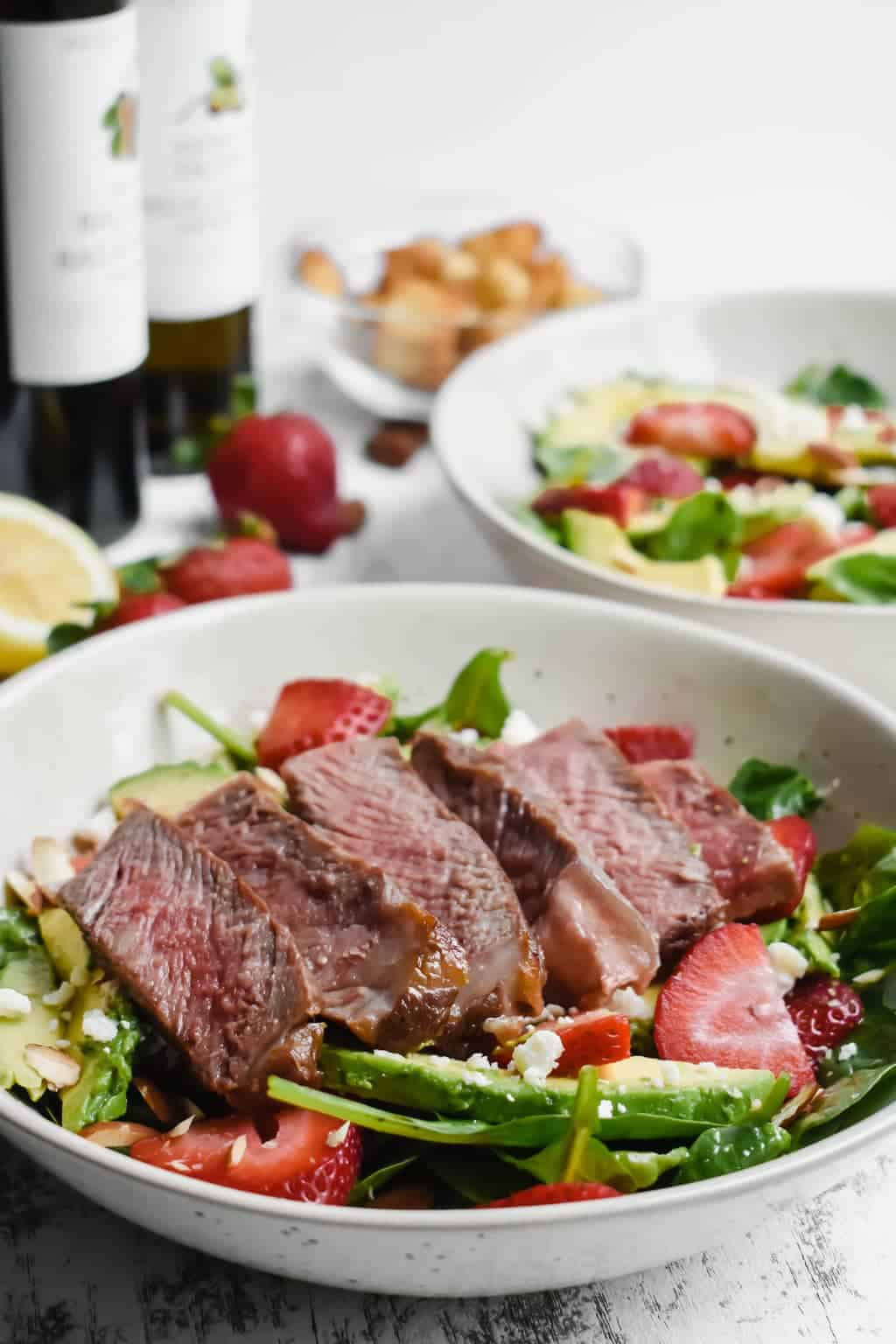 spinach salad with strawberries, avocado and steak in white bowls