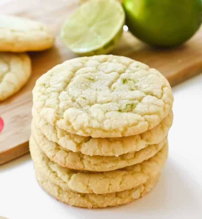 Chewy margarita cookies stacked on a white surface with limes and tequila