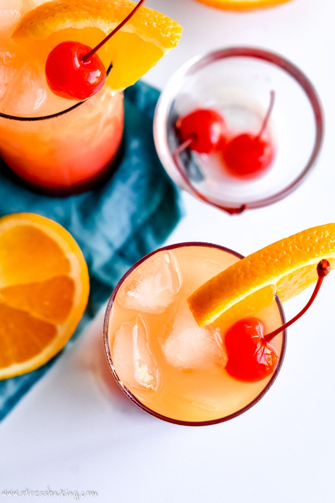 Tequila sunrise cocktails on a white surface with a teal napkin and orange slices