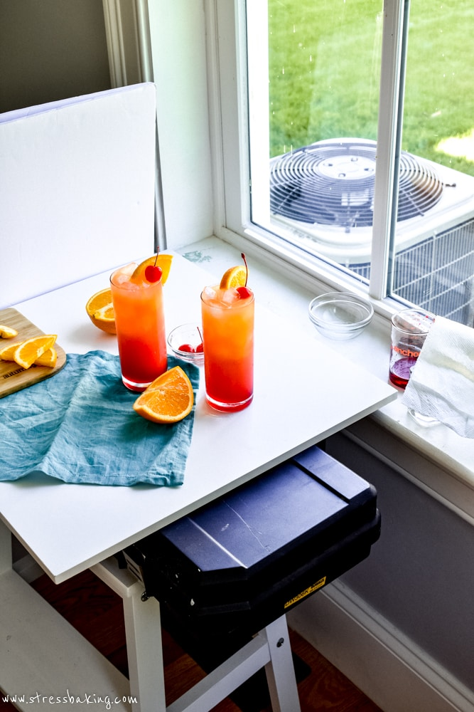 Tequila sunrise cocktails on a white surface next to a window