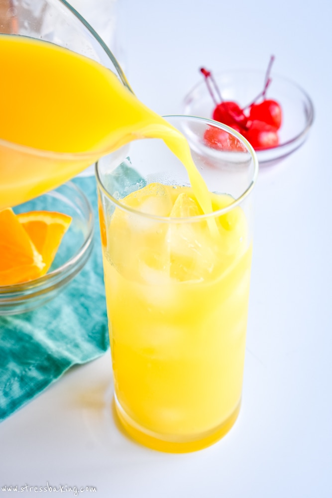 Orange juice being poured into a highball glass