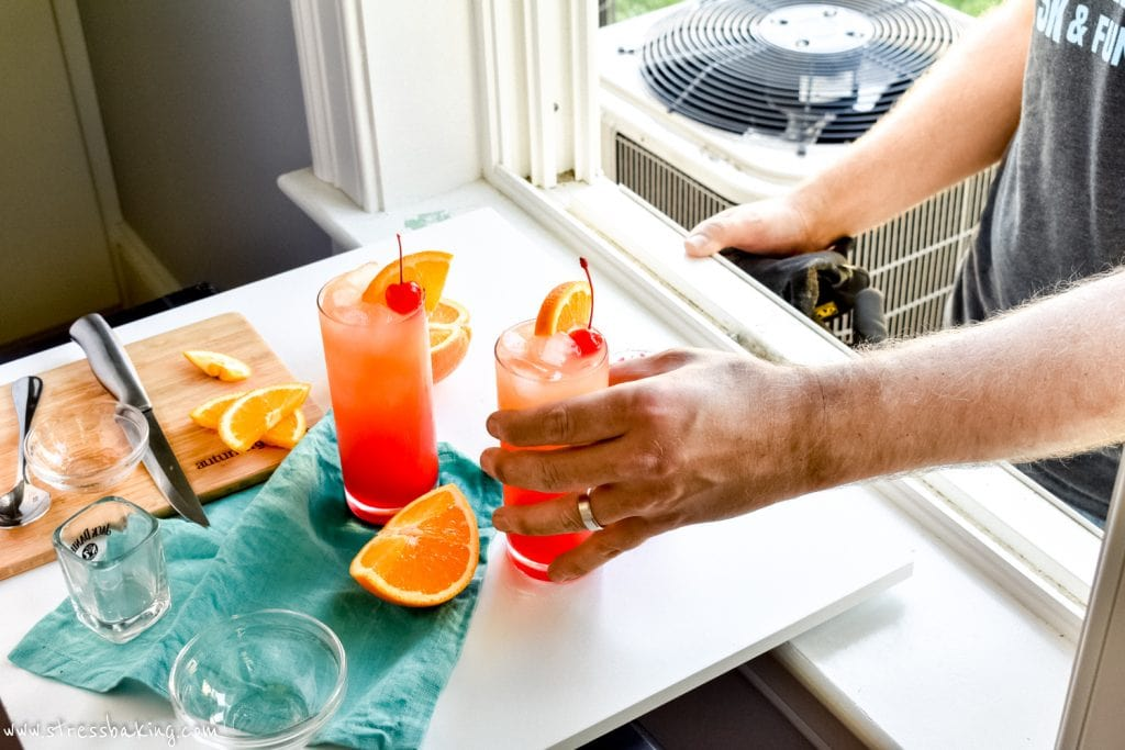 Hand grabbing a tequila sunrise cocktail off a white surface