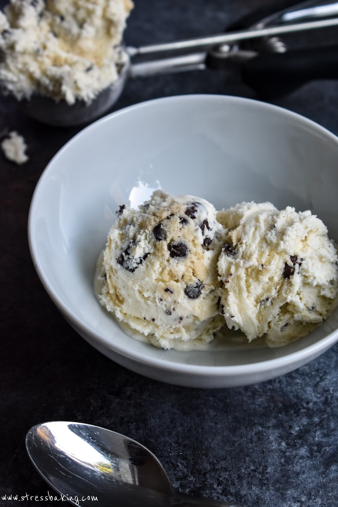Two scoops of chocolate chip cookie dough ice cream in a white bowl