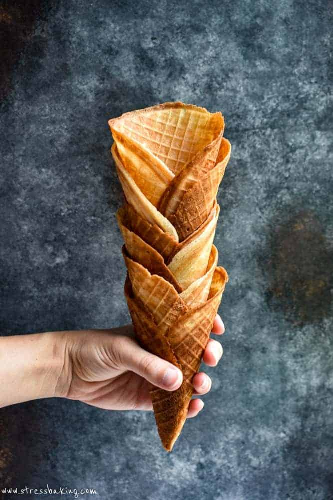 Waffle cones stacked and being held against a dark background