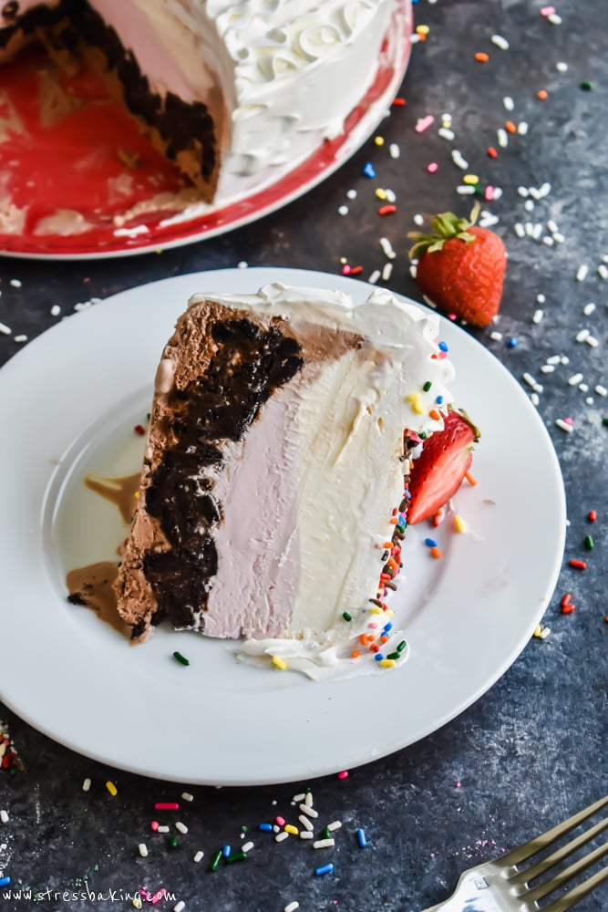 A slice of Neapolitan Crunch Ice Cream Cake on its side on a white plate