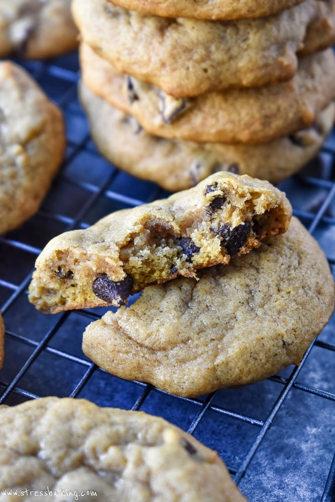 A pumpkin chocolate chip cookies on a wire rack and dark background with a bite taken out showing the chewy and soft inside