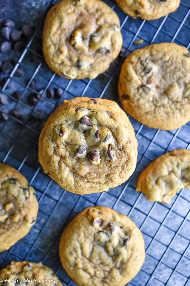 Overhead shot of a stack of chewy pumpkin chocolate chip cookies on a wire rack and dark background