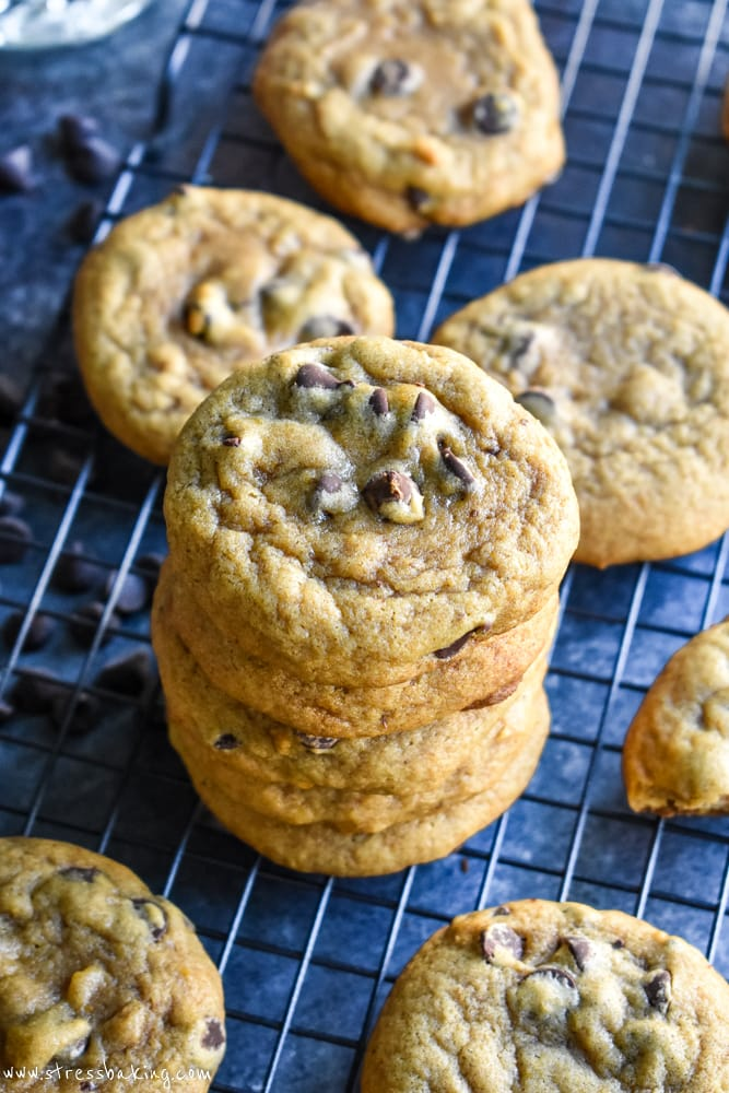 Stack of chewy pumpkin chocolate chip cookies on a wire rack and dark background