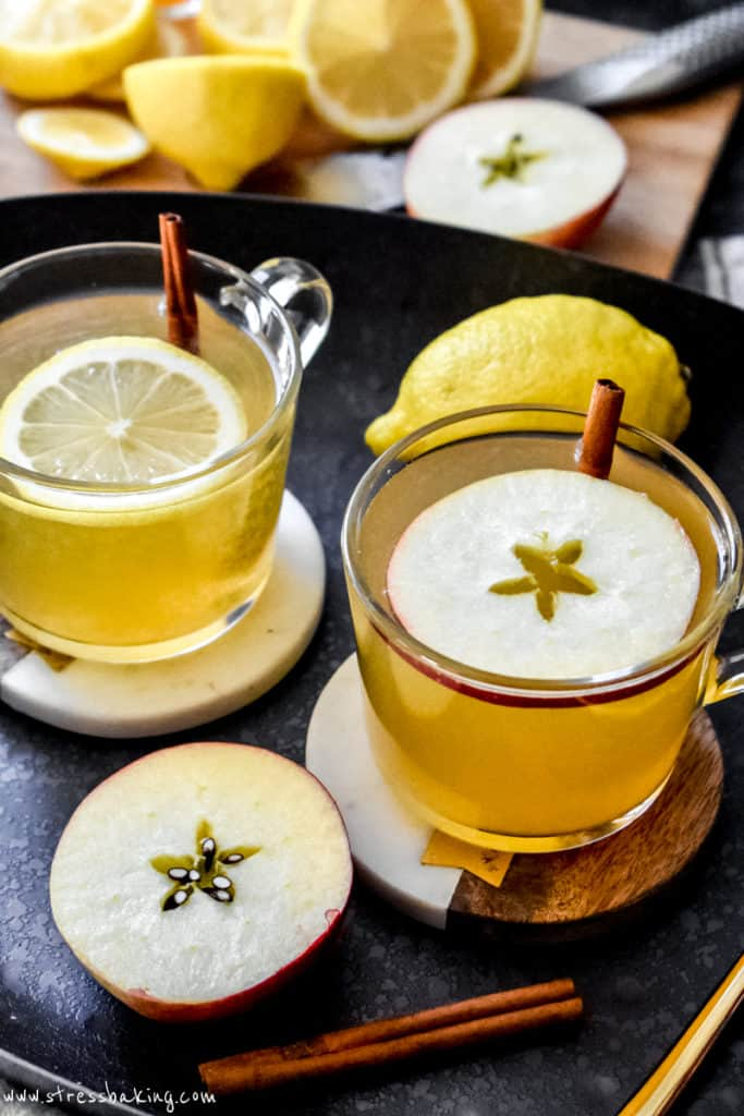 Two hot toddies in clear mugs topped with fruit garnishes