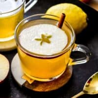 Hot toddy in a clear mug topped with apple slice