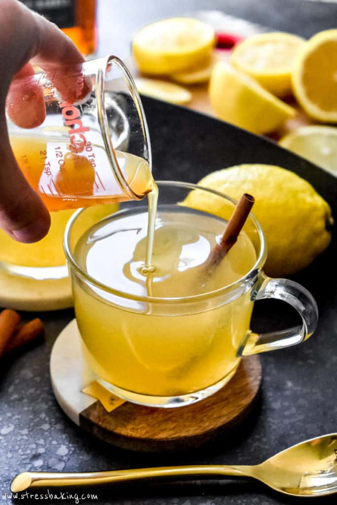 Pouring apple cider into a hot toddy in a clear mug