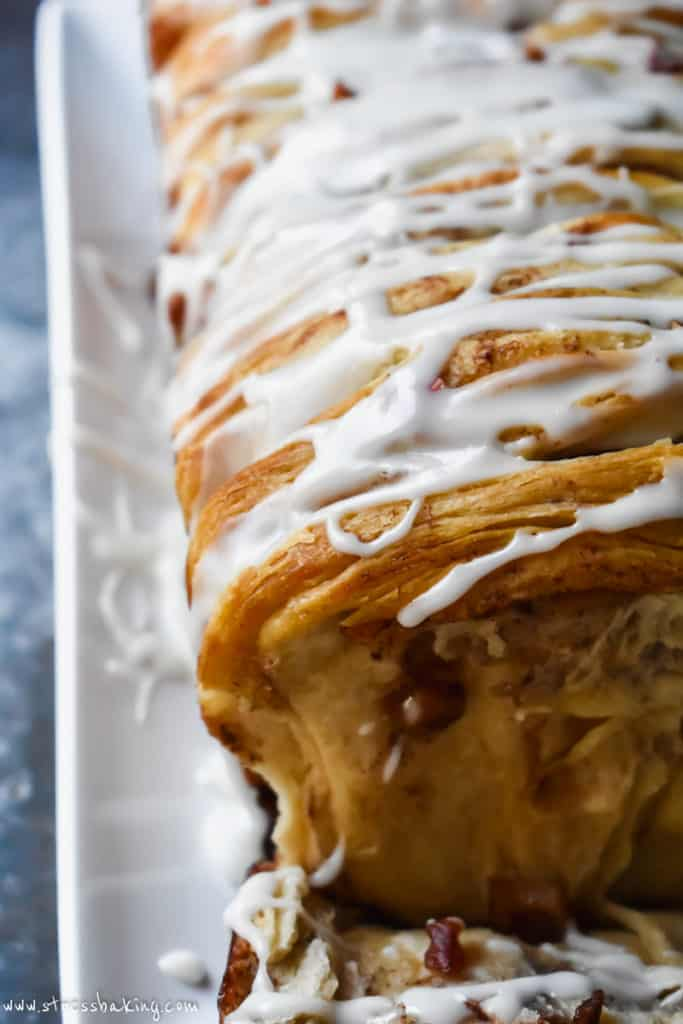 Close up side angle shot of white icing dripping down the side of a golden brown loaf of monkey bread
