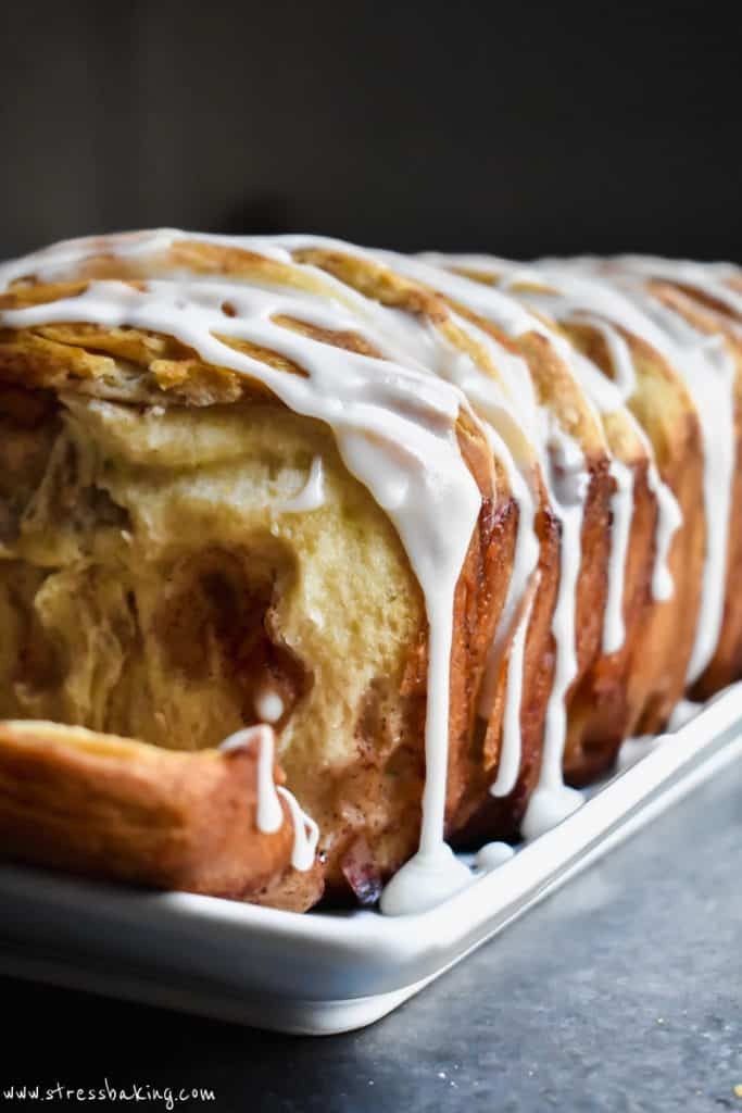 Side angle shot of white icing dripping down the side of a golden brown loaf of monkey bread