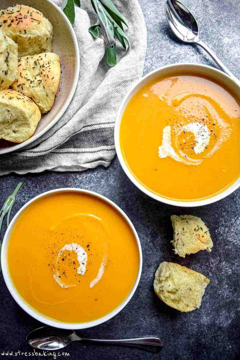 Overshot shot of two bowls of vibrant orange butternut squash soup in white bowls with swirls of coconut milk