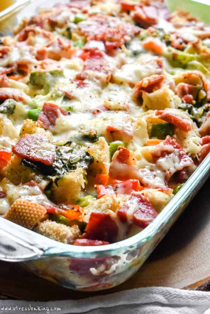 An angled shot of colorful ham and cheese strata with peppers, spinach and cheese