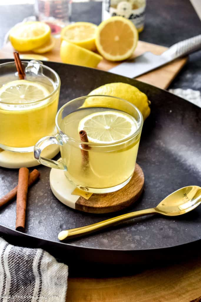 Hot toddy in a clear mug topped with lemon slice and cinnamon stick next to spoon