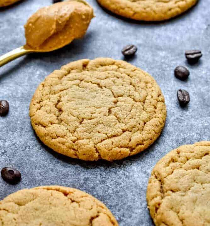 Crinkly peanut butter espresso cookies on a baking sheet with espresso beans and a spoon of peanut butter