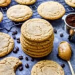 A stack of peanut butter espresso cookies on a baking sheet surrounded by espresso beans and a spoon of peanut buttr