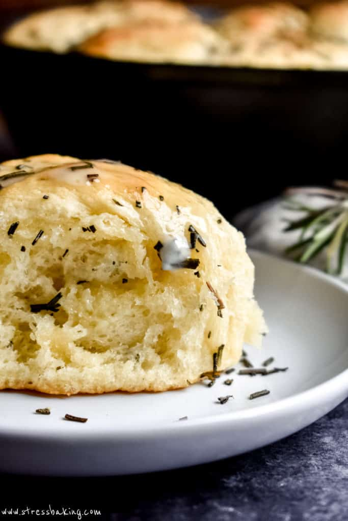 Close up of a golden dinner roll covered in melted butter and chopped rosemary