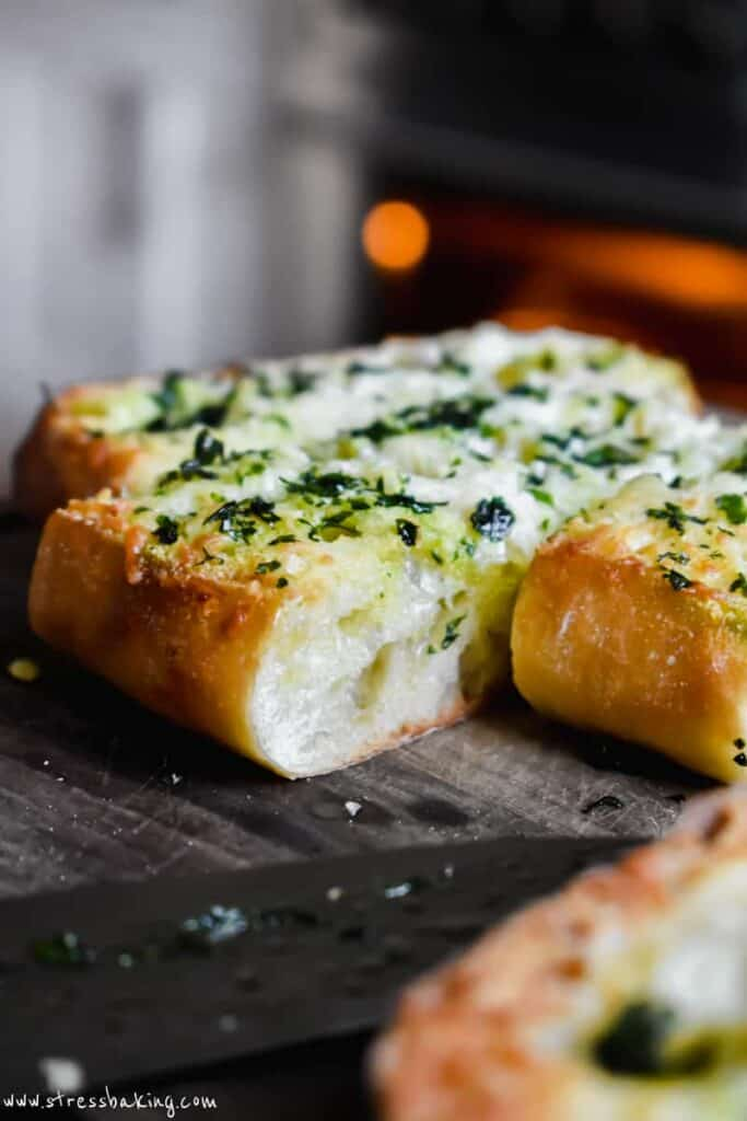 Side shot of cheesy slices of garlic bread with golden crusts