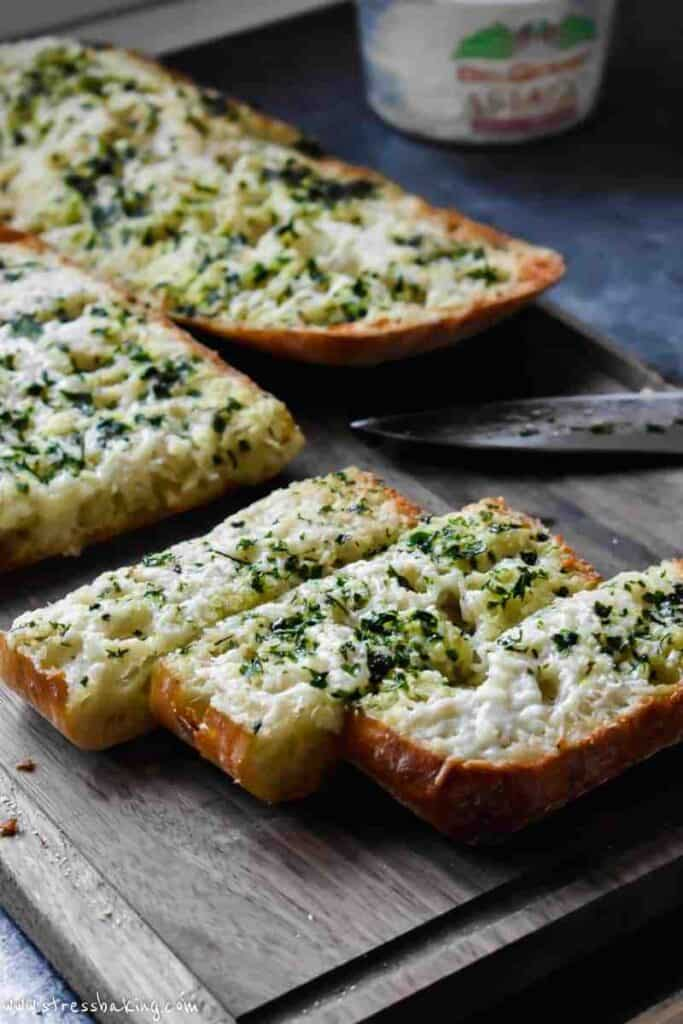 cheesy slices of garlic bread on a cutting board