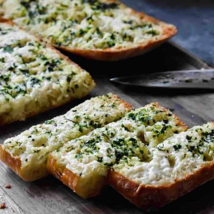 cheesy slices of garlic bread on a cutting board