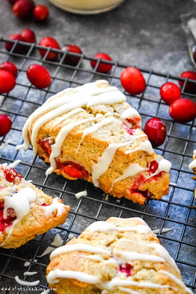 A vibrant cranberry scone on a black wire rack topped with a large drizzle of white vanilla icing surrounded by cranberries