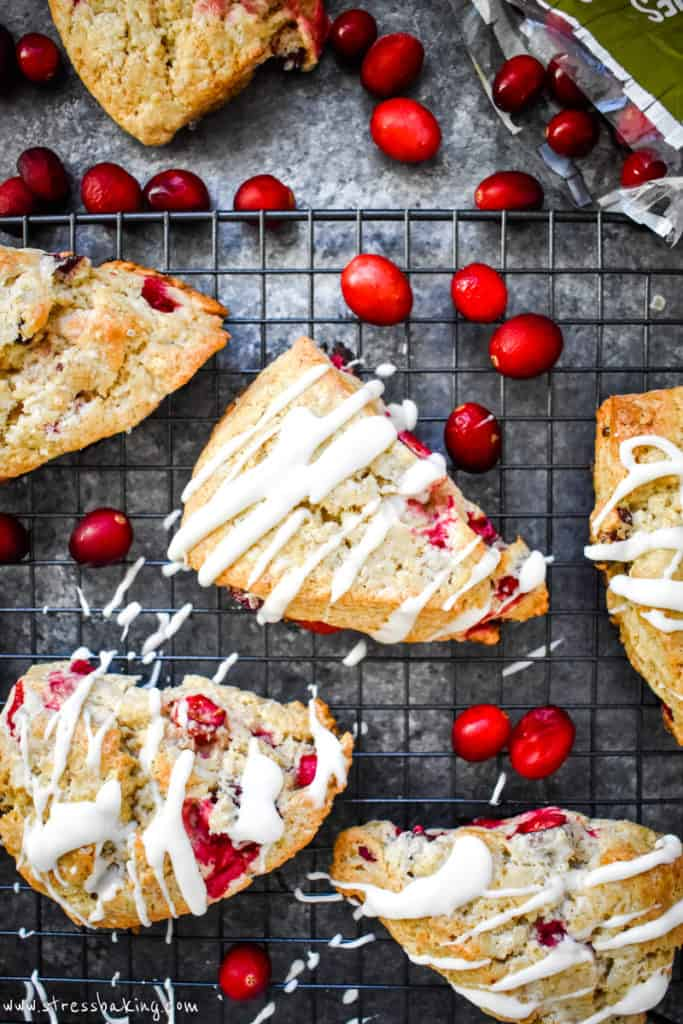 Overhead shot of cranberry scones on a black wire rack surrounded by fresh red cranberries