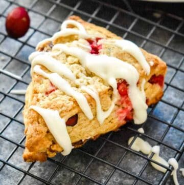 A vibrant cranberry scone on a black wire rack topped with a large drizzle of white vanilla icing