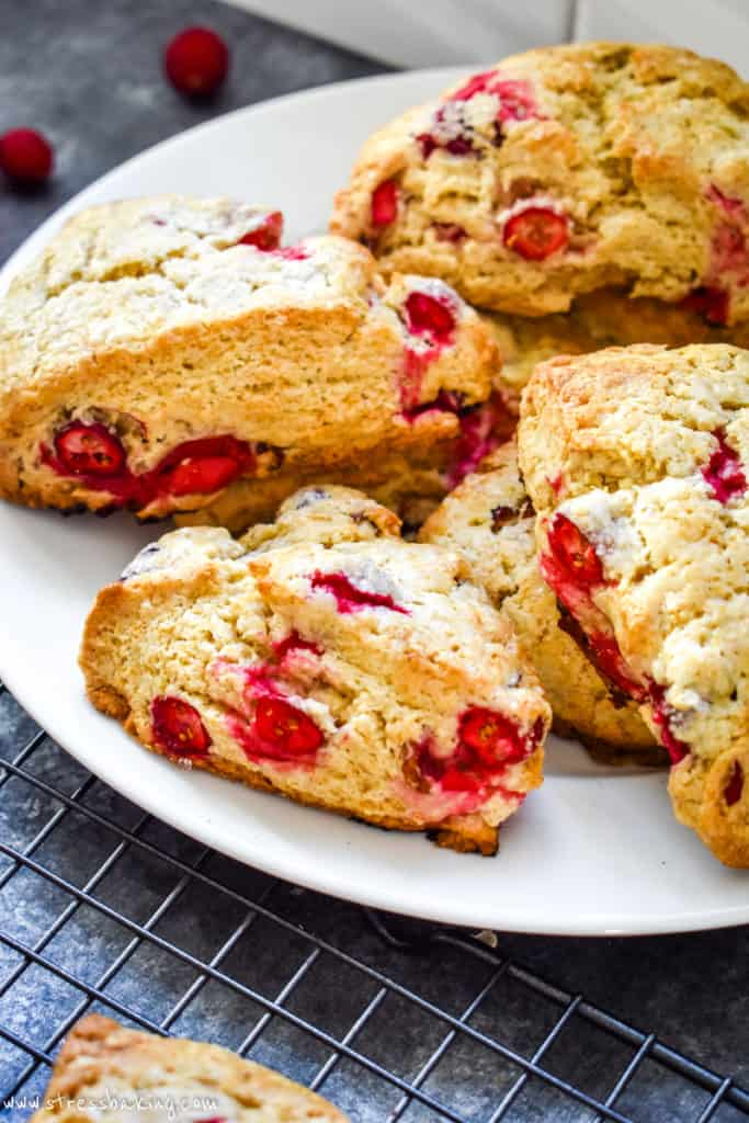 Angled shot of many vibrant cranberry scones on a white plate