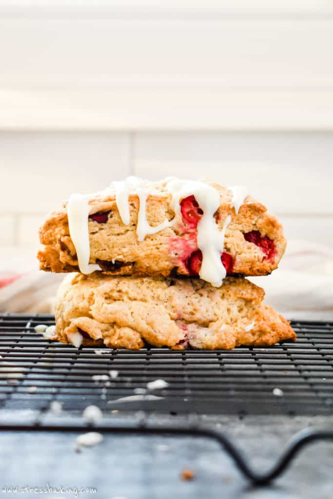 Side shot of two cranberry scones stacked on a black wire rack and topped with white vanilla icing