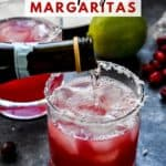 Champagne being poured into a glass of cranberry champagne margarita