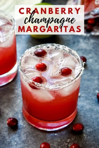 A vibrant red cranberry champagne margarita in a clear glass garnished with fresh cranberries