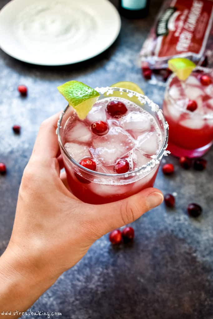 A hand holding a vibrant red cranberry champagne margarita