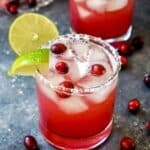 A vibrant red cranberry champagne margarita in a clear glass garnished with fresh cranberries and a lime wedge