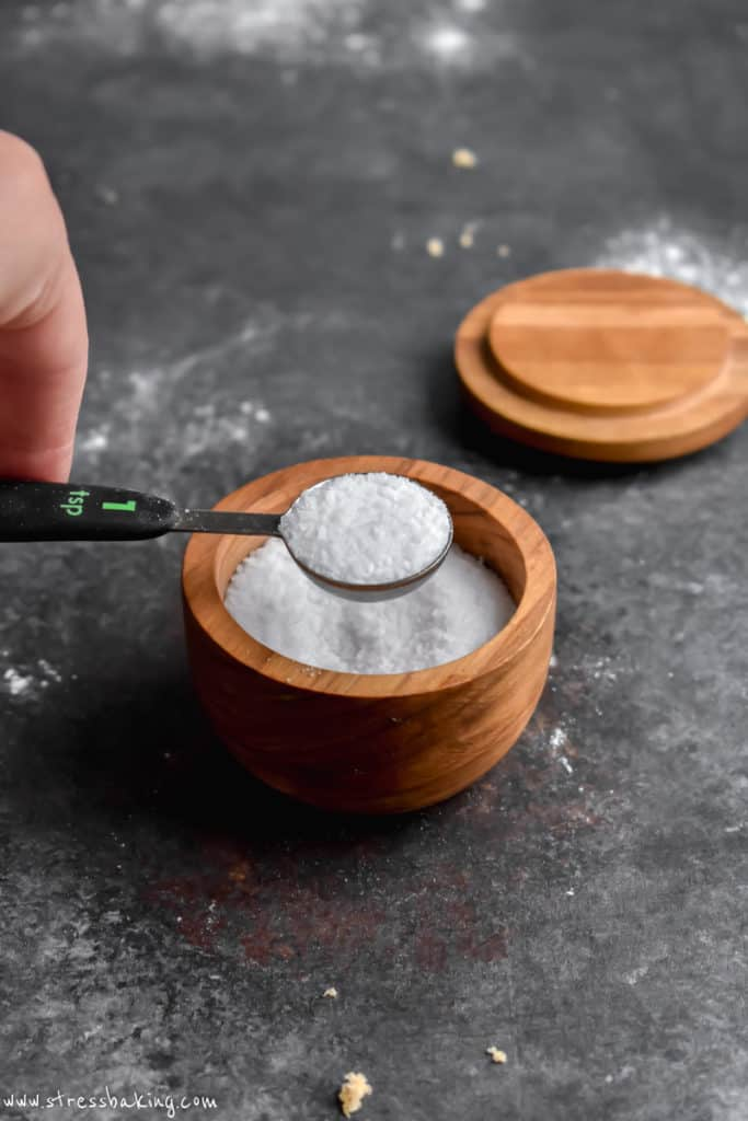 A measuring spoon holding salt over a salt cellar