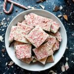 Overhead shot of peppermint bark pieces stacked on top of each other in a white bowl
