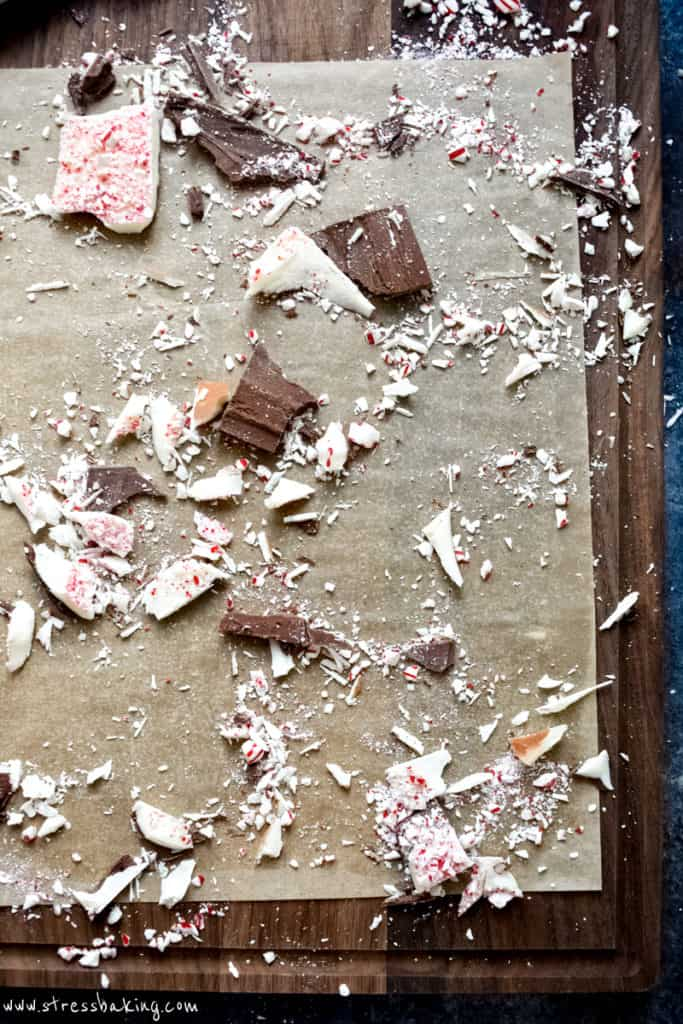 Leftover peppermint bark pieces on parchment paper on a cutting board