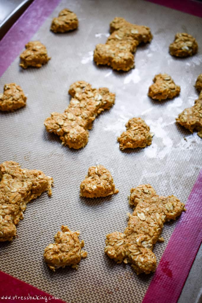 A baking sheet of pumpkin peanut butter dog treats shaped like bones and hearts