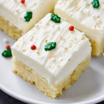 A sugar cookie bar on a white plate decorated with white frosting and festive sprinkles