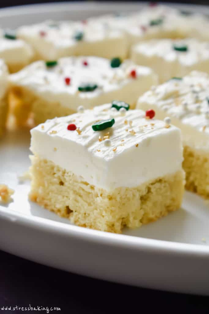 Sugar cookie bars on a white plate decorated with white frosting and festive sprinkles