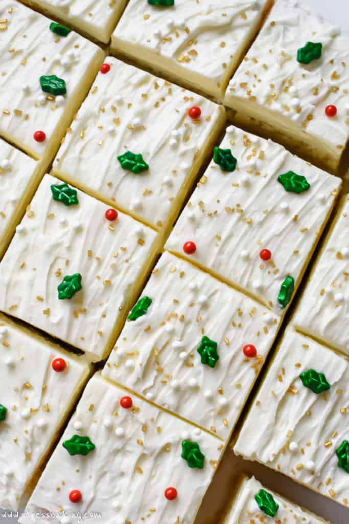 Overhead shot of sugar cookie bars on a white plate decorated with white frosting and festive sprinkles