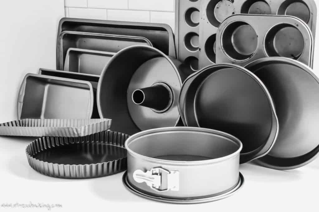Counter full of different sized and shaped metal baking pans