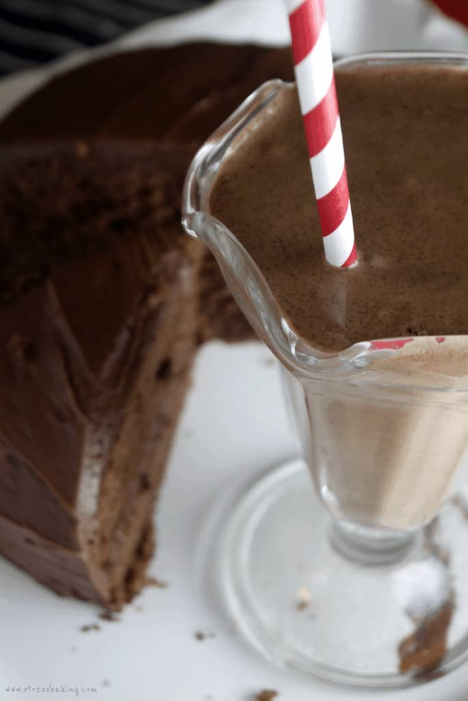 A chocolate cake shake with a red and white striped straw next to chocolate cake
