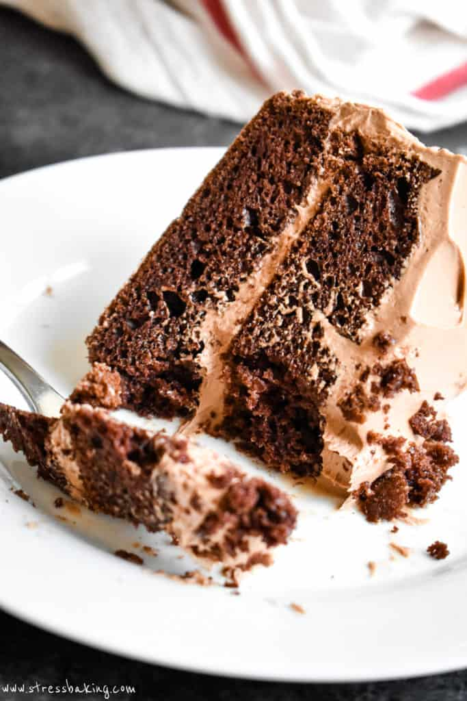 Close up of a slice of two layer chocolate cake on a white plate with a fork and a bite taken out