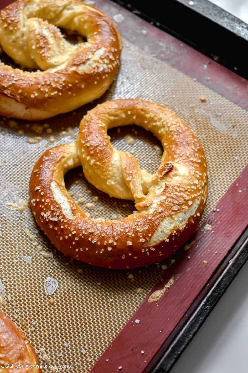 Golden brown soft pretzel covered in salt on a silicon mat