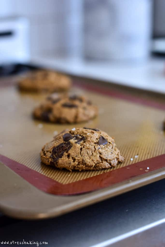A chocolate chip cookie puffed up on a baking sheet