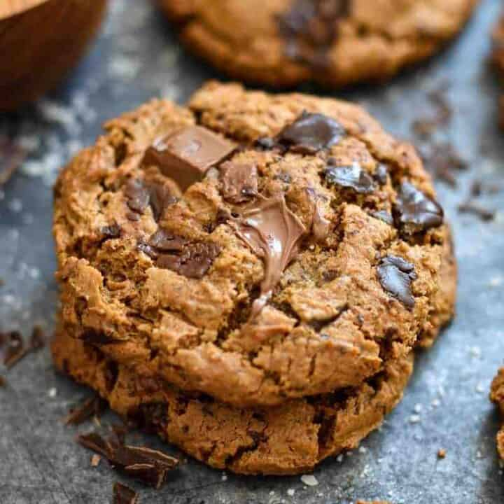 A stack of paleo chocolate chip cookies on a baking sheet